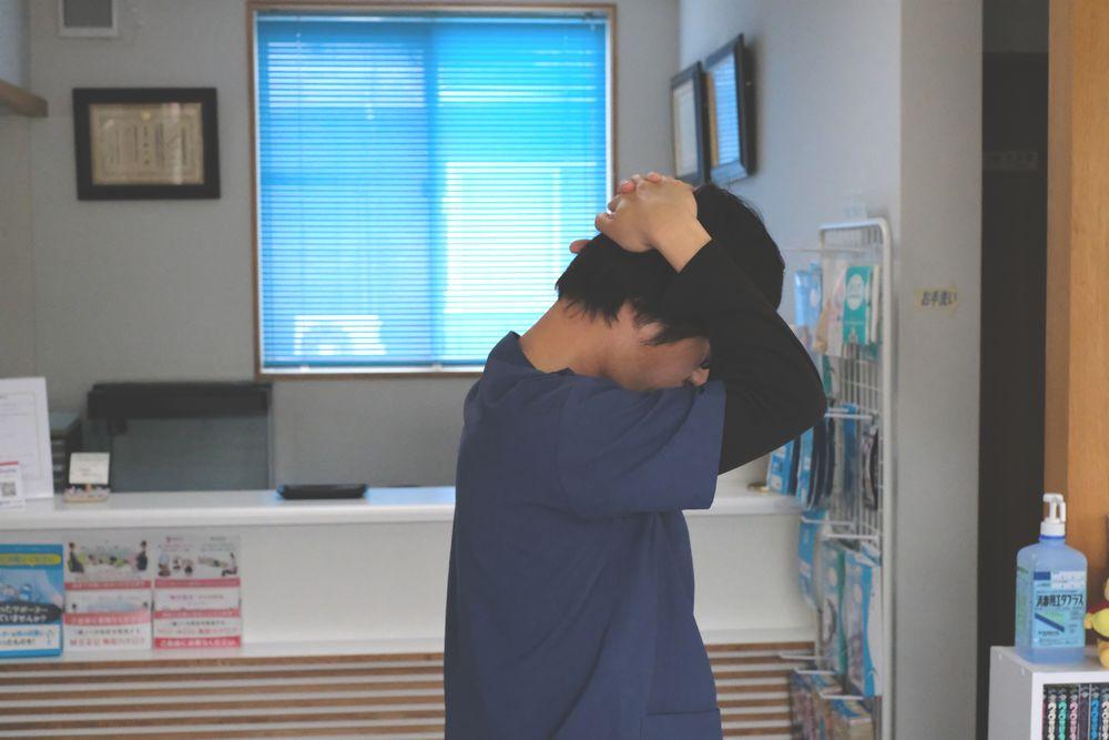 首の後ろを伸ばすときは、頭の上の方を押さえてゆっくり前に倒します。